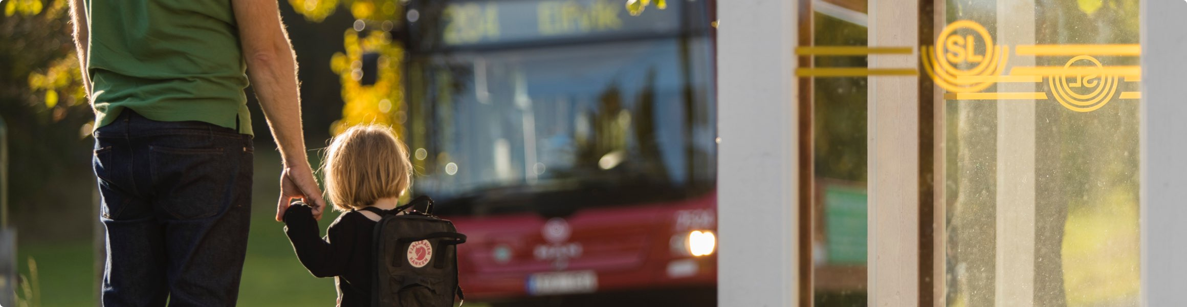 Vuxen som håller ett barn i handen och en buss i bakgrunden