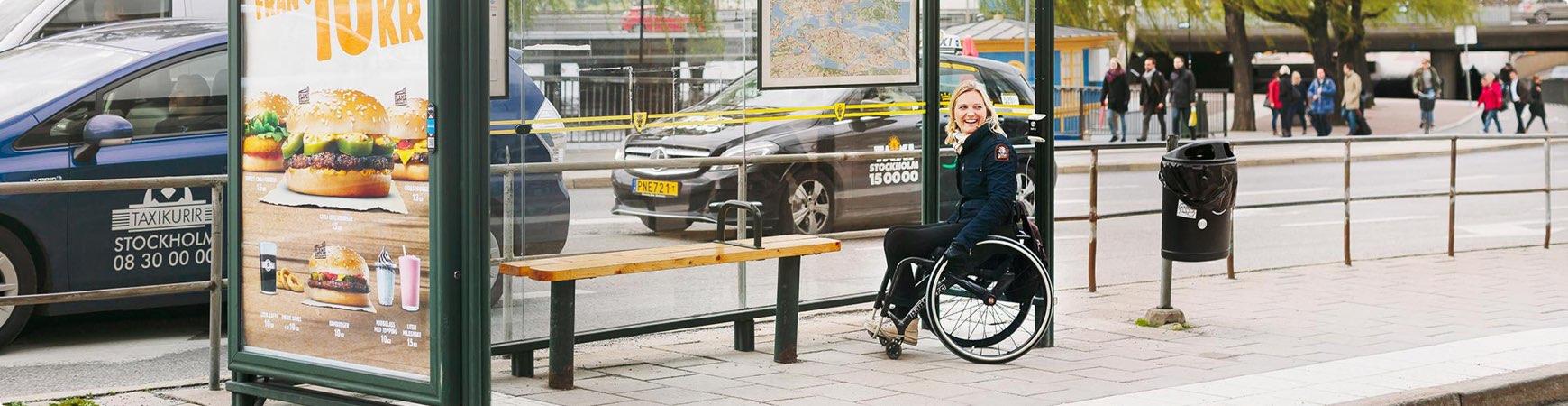 Glad person väntar på bussen