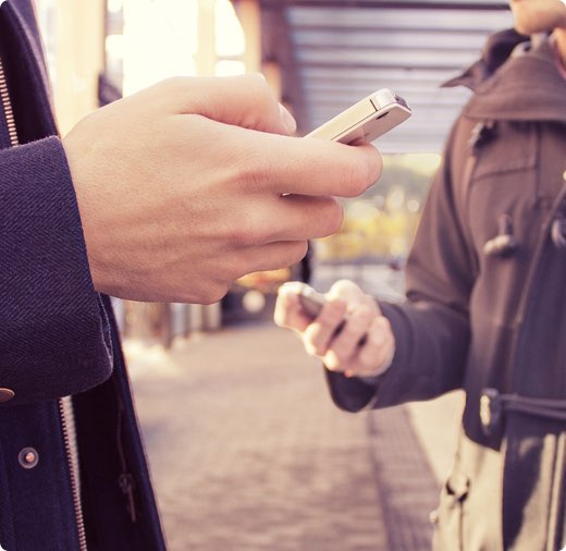 Två händer håller i mobiltelefoner