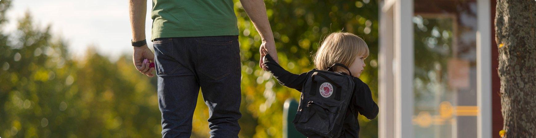 Vuxen och barn håller hand vid busshållplats