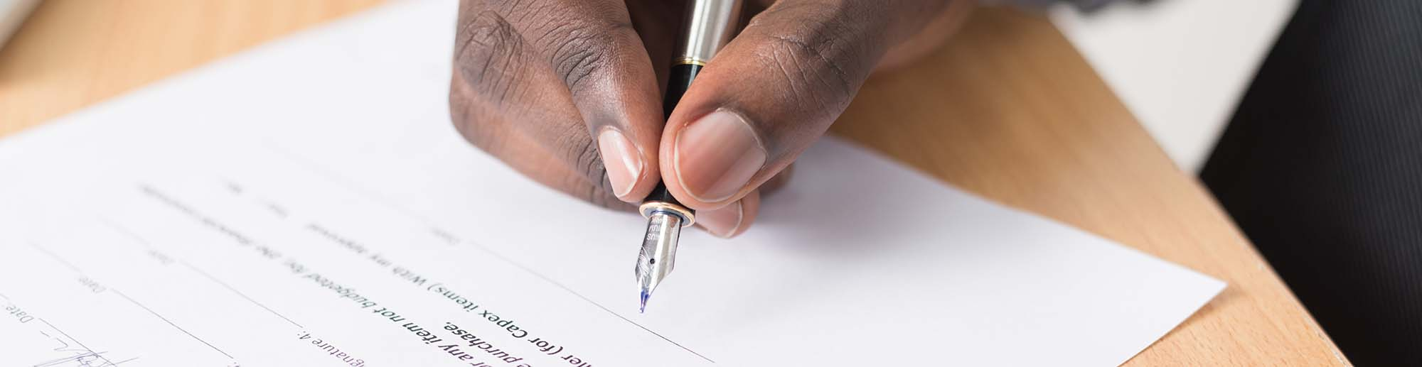 Hand skriver under på papper